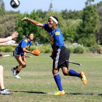 The UCLA Ouidditch team player passing the quaffle to another teammate hoping to score a goal to win the match.