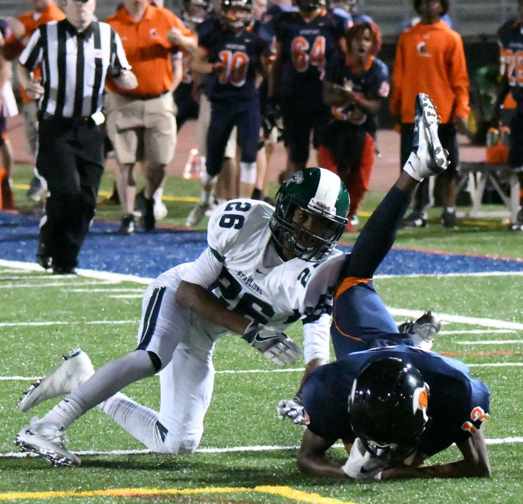 WS Varsity football player goes up against Sputh Country's defender in a fall game earlier this year. The helmets that both players wear help to protect them from clashes like this one.