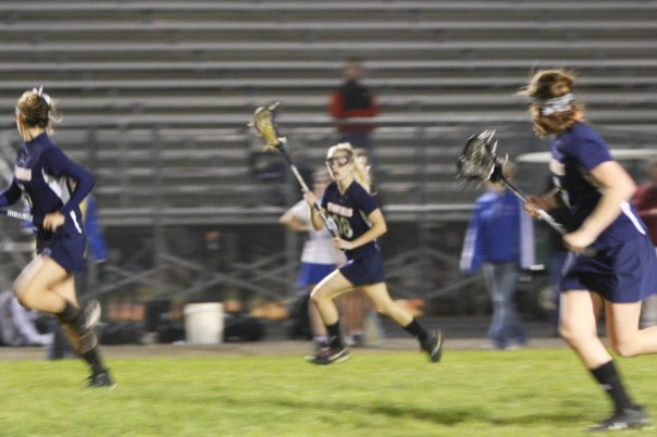 Katie Tinsley, number 18, cradles the lacrosse ball in her stick as she runs it down the field, back when she played on the WS girls' lacrosse team. Tinsley now coaches the JV girls' team along with Alexa Romano.