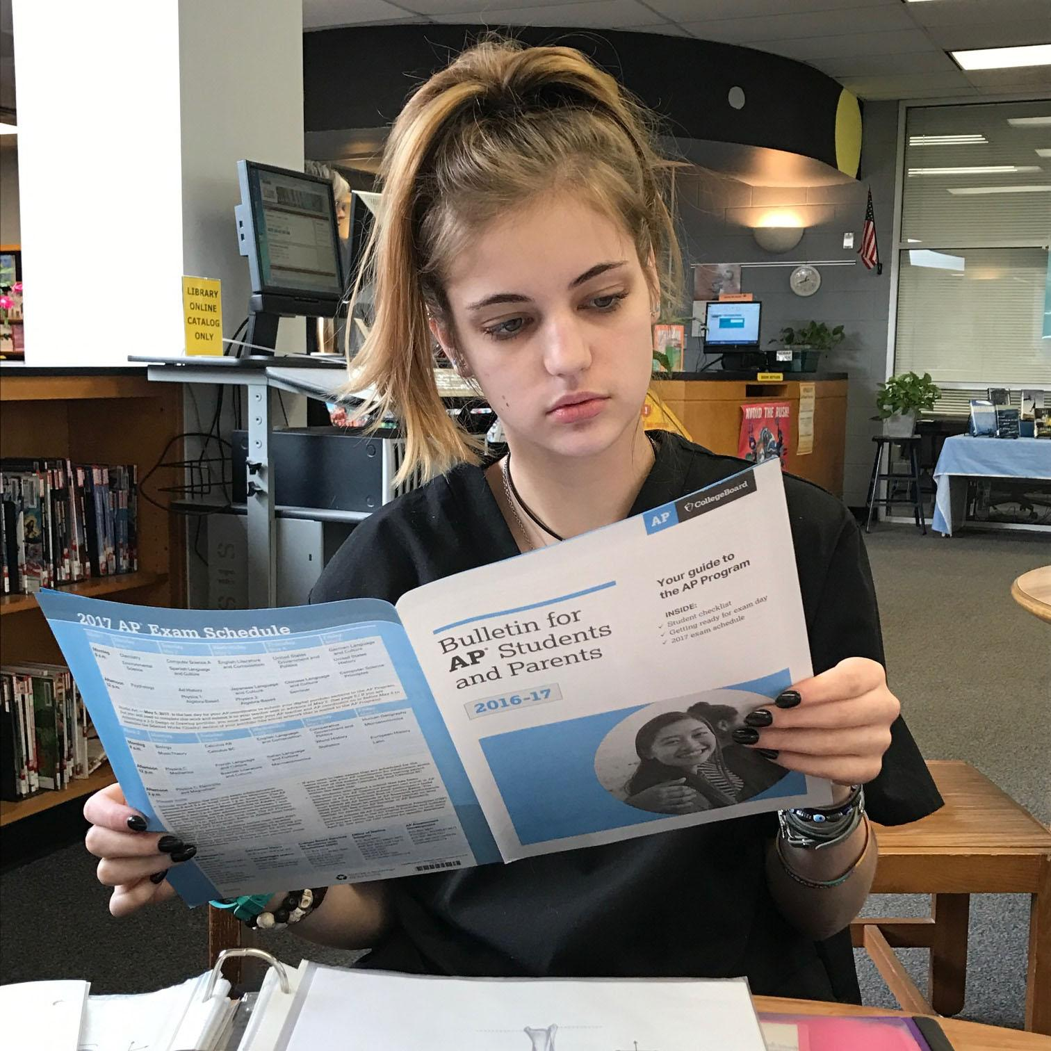 Senior Elise Roberts reads over the Bulletin for AP Students and Parents. It contains essential information such as what to expect, the 2017 testing schedule, and what to bring to for testing.