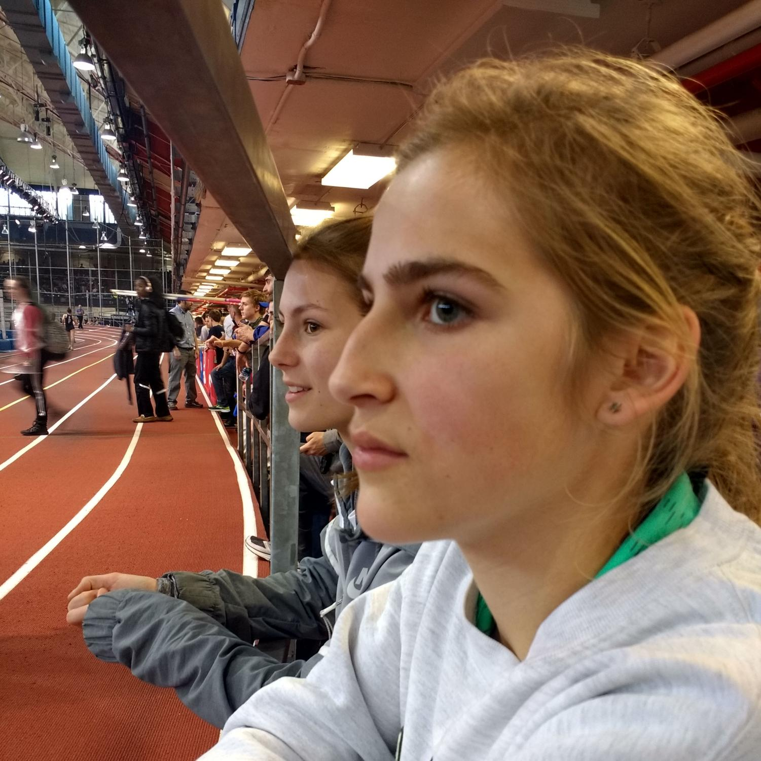 Sophomores Katie Orchard and Amy Herrema watch a track meet while thinking of all the homework they have to do.