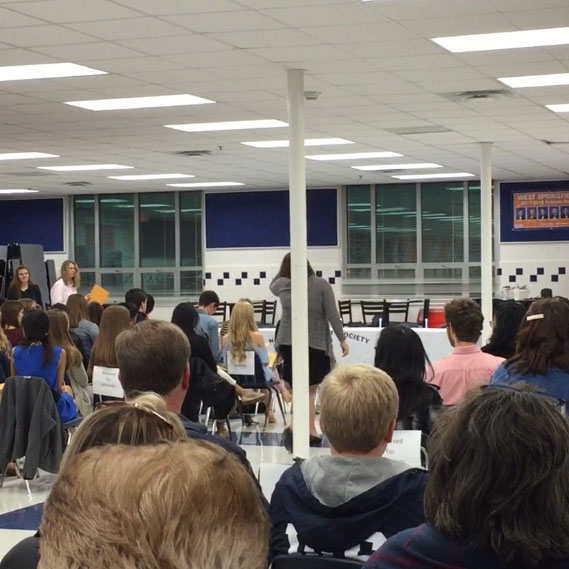 Family members and peers look as the induction ceremony takes place in the new cafeteria.