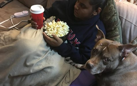 Senior Elina Vancini cuddles with her dog and a bowl of popcorn ready to enjoy a holiday movie marathon. There are a variety of movies for students to enjoy beyond the