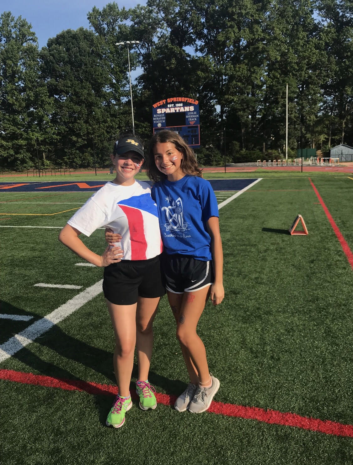 Juniors Eliza Snipes (left) and Vivian Santiago (right) on the football field after practice. Santiago, who is on the Color Guard, and Snipes, who is in the Marching Band, spent over eight hours each day practicing in the hot August heat.
