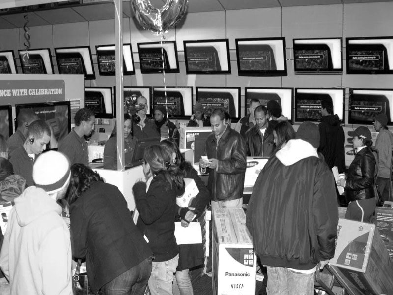 Shoppers mob a Black Friday electronics sale. The aggressive consumption that is promoted by America's corporations contradicts the values of giving that the holiday season is all about. Focus not on getting a great deal on an expensive gift, but getting your loved ones something meaningful this holiday season.