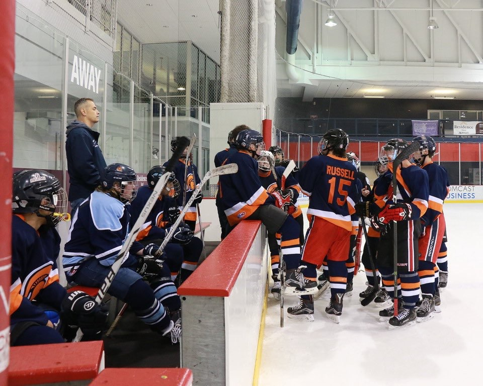 The hockey team huddles together while a timeout is called on the ice during their game against Lake Braddock.
