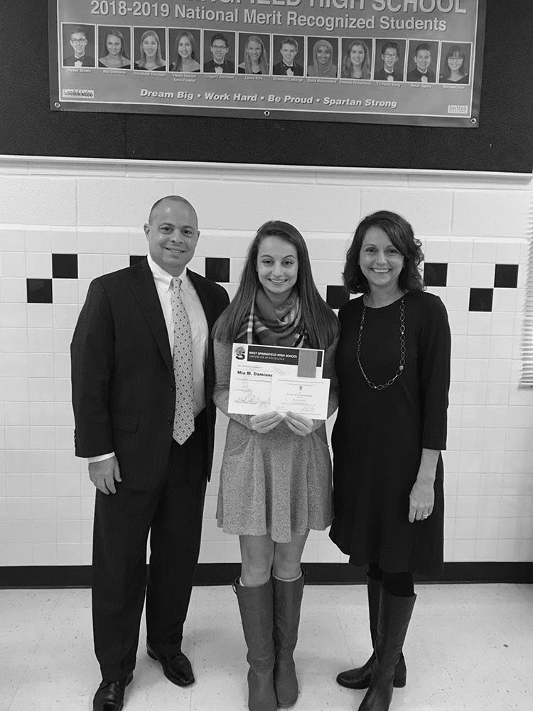 Senior Mia Damiano holds her certificates and poses for a photo with her parents. Damiano won both an AP Scholar Award and was commended for her performance on the PSAT/NMSQT