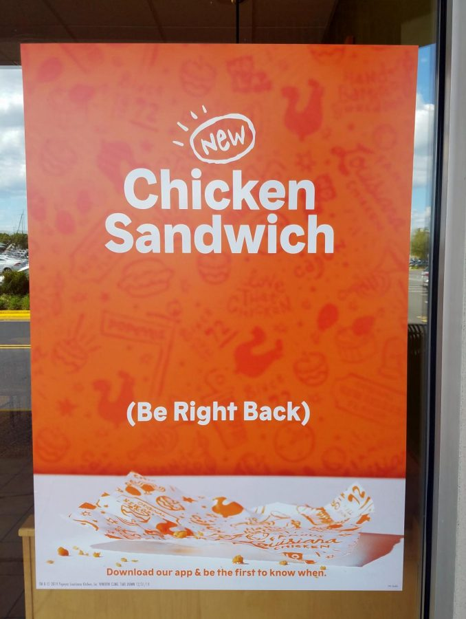 A poster on the outside of a Popeyes restaurant informs unsuspecting customers of the lack of sandwiches. The common message sends many disappointed customers away.
