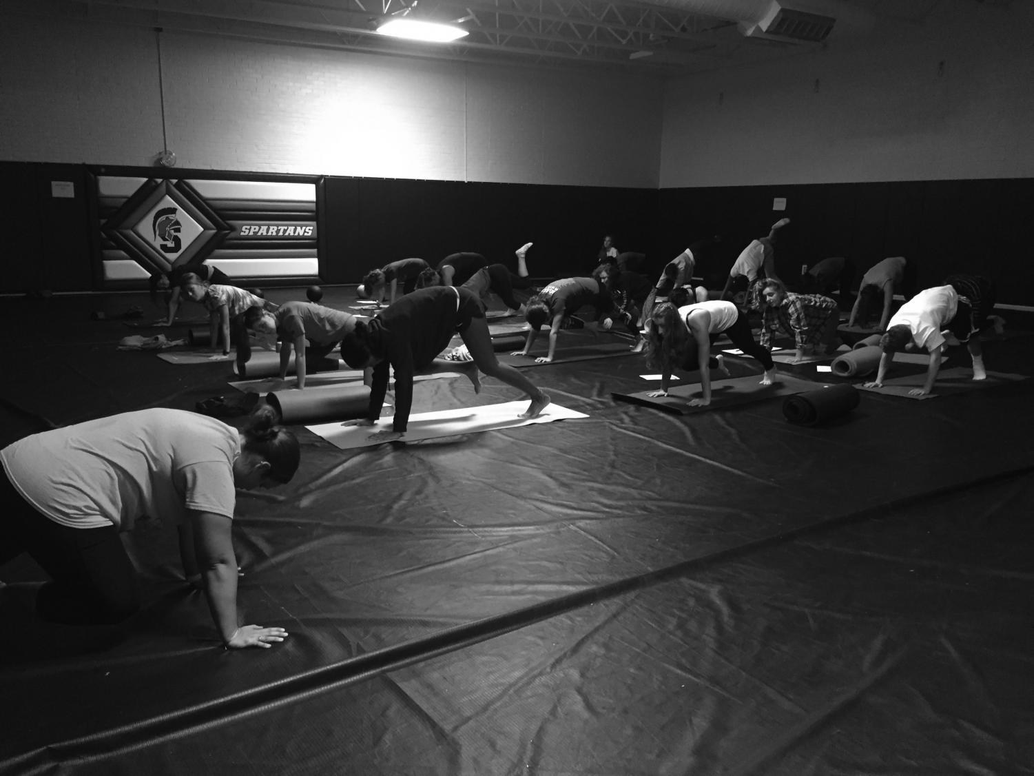 Rosie Donaldson teaches her sixth period yoga class in the wrestling room. Yoga consists of many stretches and poses and is beneficial to both one's overall physical and mental health.