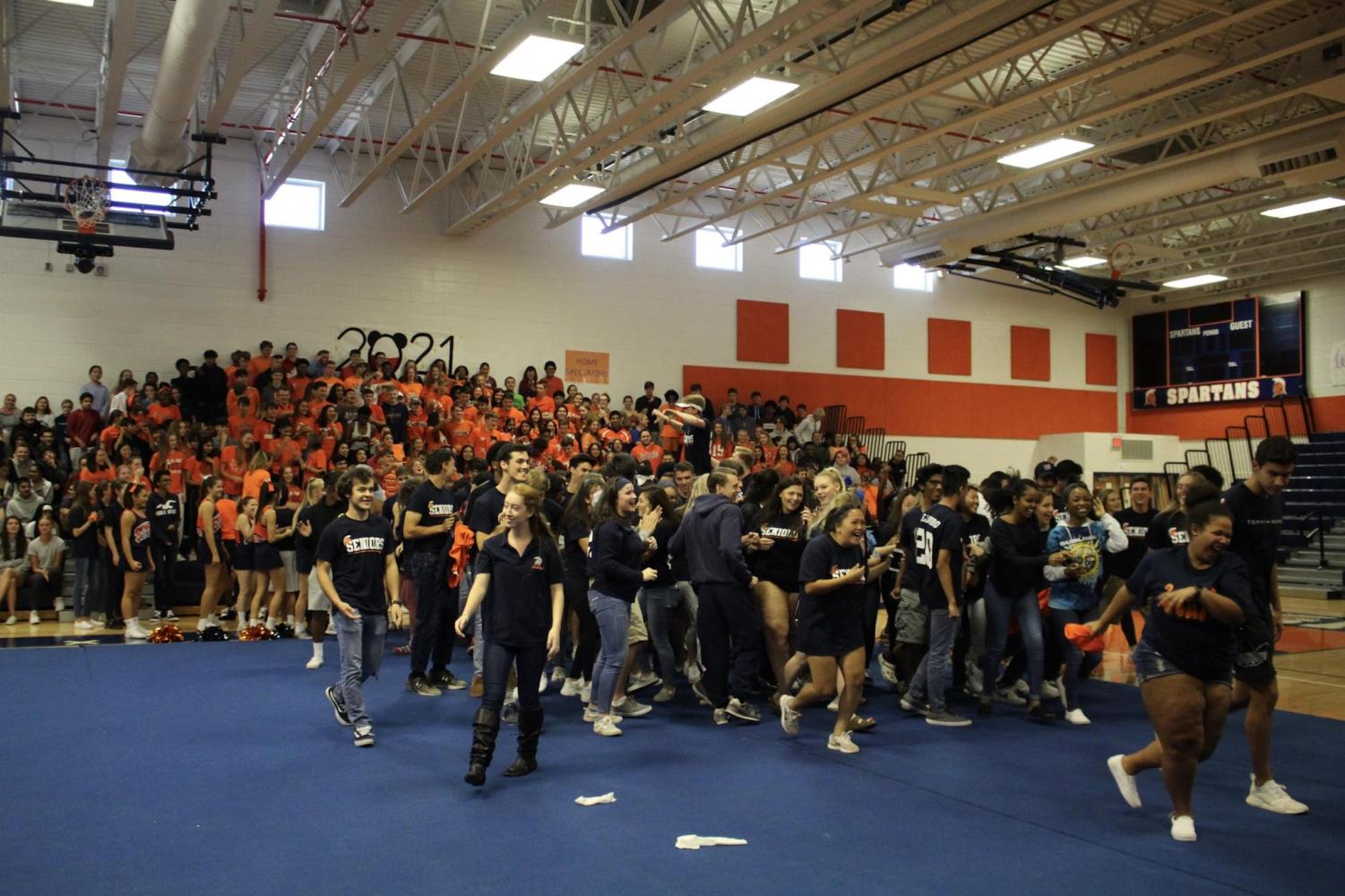 Seniors and Juniors wearing navy and orange on the class colors spirit day as they attend the Homecoming Pep Rally on Thursday.