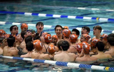 The swim team gathers for their pre-meet cheer in whey they progressively yell louder and louder until they are screaming at the top of their lungs in order to get themselves fired up for their meet.
