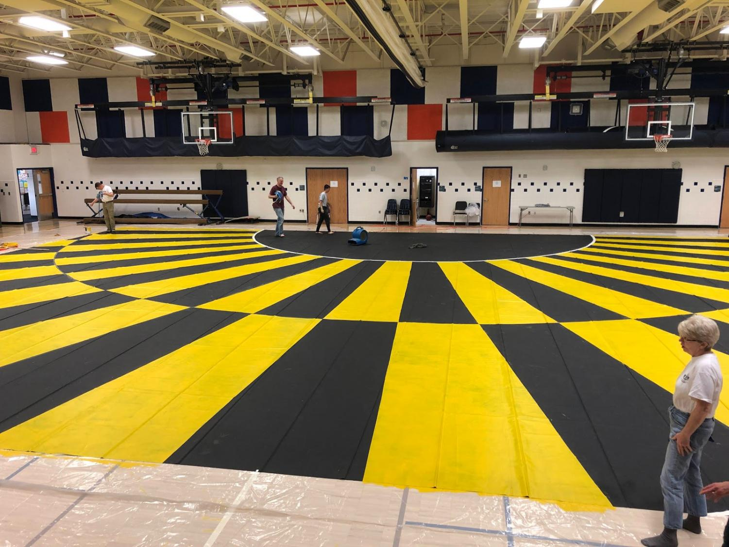The winterguard floor has a black and yellow pattern. The design is meant to be reminiscent of art deco because the theme of the show is jazz/1920s.